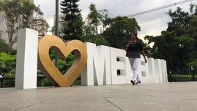 Frau, die herein vor Zeichen Medellin geht stock video footage