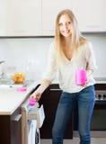 Frau, die herein Weißkocher zur Waschmaschine setzt Lizenzfreie Stockfotografie