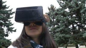 Frau, die herum im Park unter Verwendung VR-Kopfhörers schaut stock video footage