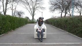 Frau, die herum schaut und sich draußen mit Gläsern der virtuellen Realität - VR entspannt stock video footage