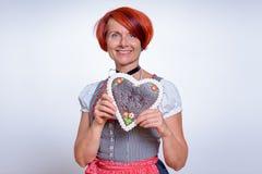 Frau, die Herz-geformtes Lebkuchen-Plätzchen hält Stockbild