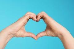 Frau, die Herz mit ihren Händen auf Farbhintergrund macht lizenzfreie stockfotografie