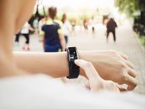 Frau, die Herzfrequenz-Übungs-Trainingseignung Smart im Freien überprüft Stockbilder