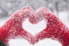Frau, die Herzsymbol mit den schneebedeckten Händen macht Stockfoto