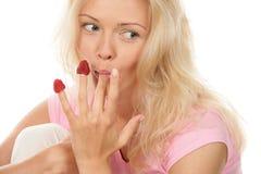Frau, die Himbeeren weg von den Fingern isst Lizenzfreie Stockbilder