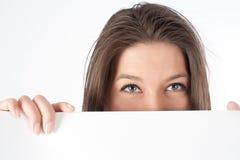 Frau, die hinter Anschlagtafel sich versteckt Lizenzfreies Stockbild