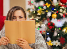 Frau, die hinter Buch nahe Weihnachtsbaum sich versteckt Stockbild