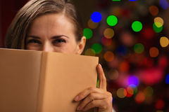 Frau, die hinter Buch nahe Weihnachtsleuchten sich versteckt Stockbilder