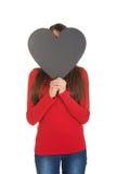 Frau, die hinter dem Herzen gemacht vom Papier sich versteckt Lizenzfreies Stockbild