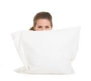 Frau, die hinter dem Kissen getrennt auf Weiß sich versteckt Lizenzfreies Stockfoto