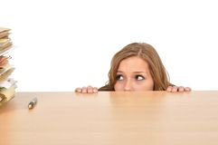 Frau, die hinter dem Schreibtisch sich versteckt Lizenzfreie Stockfotos