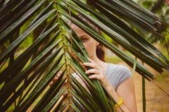 Frau, die hinter den Palmblättern sich versteckt Stockfotografie