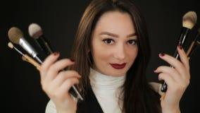 Frau, die hinter Make-upbürsten sich versteckt stock footage