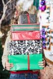 Frau, die hinter Stapel Weihnachtsgeschenken sich versteckt Stockfoto