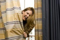Frau, die hinter Trennvorhängen sich versteckt Lizenzfreies Stockfoto