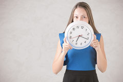 Frau, die hinter Uhr sich versteckt Stockbilder