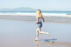 Frau, die hinunter den Strand in der Sommersaison läuft lizenzfreie stockfotografie