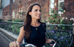 Frau, die hinunter die Straße mit einem Zyklus geht Stockbild