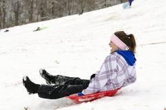 Frau, die hinunter schneebedeckten Hügel 3 rodelt Stockbild