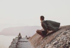 Frau, die Horizont in Monolithos, Rhodos, Griechenland sitzt und betrachtet lizenzfreie stockfotografie