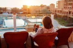 Frau, die am Hotelbalkon genie?t Sonnenaufgang mit Swimmingpool- und Seeansicht sich entspannt lizenzfreie stockfotos