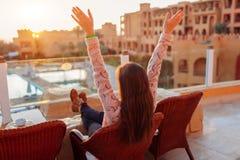 Frau, die am Hotelbalkon genie?t Sonnenaufgang mit Swimmingpool- und Seeansicht sich entspannt lizenzfreies stockfoto
