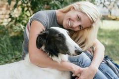 Frau, die Hund umarmt Lizenzfreie Stockfotos