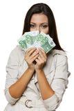 Frau, die an Ihnen über einem Gebläse der Eurorechnungen blickt Lizenzfreie Stockfotografie