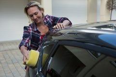 Frau, die ihr Auto mit Schwamm säubert Lizenzfreie Stockbilder