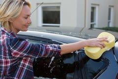 Frau, die ihr Auto mit Schwamm säubert Stockbild