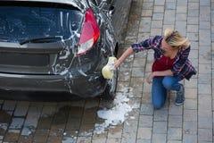 Frau, die ihr Auto mit Schwamm säubert Lizenzfreie Stockfotografie