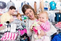 Frau, die ihr Baby im Shop trägt lizenzfreie stockbilder