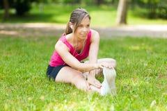 Frau, die ihr Bein beim Sitzen auf dem Gras ausdehnt lizenzfreie stockbilder