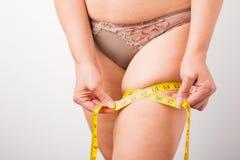 Frau, die ihr Bein ` s Fett misst lizenzfreie stockfotos