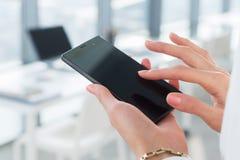 Frau, die ihr digitales Gerät, Nachrichten lesend verwendet und senden sms, surfendes Internet, blogging und apps im Büro, Nahauf Lizenzfreie Stockbilder