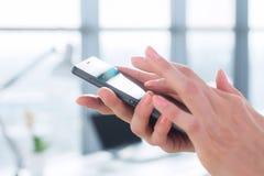 Frau, die ihr digitales Gerät, Nachrichten lesend verwendet und senden sms, surfendes Internet, blogging und apps im Büro, Nahauf Lizenzfreies Stockfoto