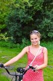Frau, die ihr Fahrrad im Holz drückt Lizenzfreie Stockbilder