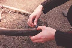 Frau, die ihr Fahrrad repariert Lizenzfreies Stockfoto