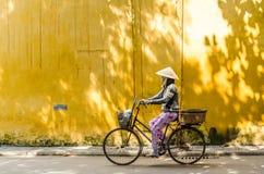 Frau, die ihr Fahrrad vor der gelben Wand reitet Lizenzfreies Stockbild