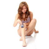 Frau, die ihr Fahrwerkbein depilating ist. Stockfotografie