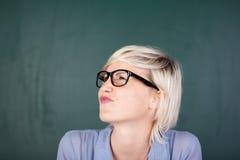 Frau, die ihr Gesicht gegen Tafel Verzerrt Stockfoto