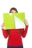 Frau, die ihr Gesicht hinter einem Notizbuch versteckt Lizenzfreies Stockfoto
