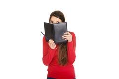 Frau, die ihr Gesicht hinter einem Notizbuch versteckt Lizenzfreies Stockbild