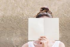 Frau, die ihr Gesicht hinter leerem Weißbuchnotizbuch versteckt Stockbild
