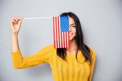 Frau, die ihr Gesicht mit amerikanischer Flagge bedeckt Stockbilder