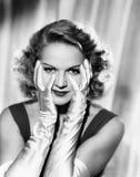 Frau, die ihr Gesicht mit den behandschuhten Händen des Satins gestaltet (alle dargestellten Personen sind nicht längeres lebende Stockfoto