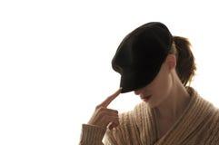 Frau, die ihr Gesicht mit einem schwarzen Hut versteckt Stockbild
