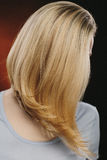 Frau, die ihr Gesicht mit ihrem blonden Haar bedeckt Stockfotos