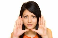 Frau, die ihr Gesicht mit ihren Palmen gestaltet Lizenzfreies Stockfoto