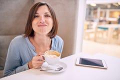 Frau, die ihr Gesicht mit lustigem Ausdruck an der Kamera zieht Lizenzfreies Stockfoto